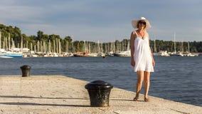 En attraktiv kvinna som bär en sommarhatt på stranden Arkivfoto