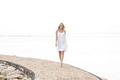 En attraktiv kvinna som går på stranden som tycker om sommar Fotografering för Bildbyråer