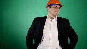 En attraktiv man i en orange konstruktionshjälm och dräkt ser kameran En ung arbetare visar gester med hans arkivfilmer