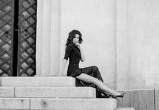 En attraktiv sexig spenslig brunett i en lång svart klänning med ett slitssammanträde på momenten av en tappningbyggnad Royaltyfri Bild