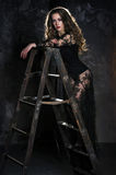 En attraktiv ung kvinna i en lång svart klänning står på en stege, en stege mot en grungevägg royaltyfria bilder
