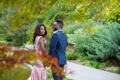 En attraktiv ung kvinna med hennes partnerinnehavhänder under härlig höst färgade trädfilialer royaltyfria foton
