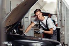 En attraktiv ung man är kontrollerande indikatorer med hjälpen av en special apparat på en bilservice och underhåll royaltyfria bilder