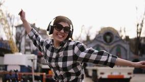 En auriculares y gafas de sol, la muchacha de moda es de baile y de salto de una manera divertida Sonrisa y risa con la boca abie almacen de video