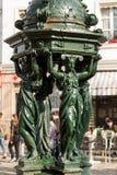 En av de dricka antika Wallace springbrunnarna med kvinnagruppskulptur på i Paris royaltyfria bilder