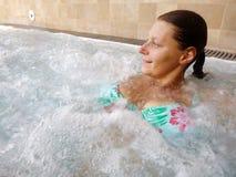 En avkopplad kvinna som gör hydromassage i en skönhetbrunnsort Royaltyfri Bild