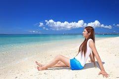 En avkopplad ung kvinna på stranden. arkivfoto