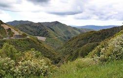 En avlägsen dal i Nya Zeeland Lastbilar är på vägen, och konstruktionsmedel fungerar fotografering för bildbyråer