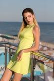 En avslappnande kvinna på en terrass på en blå havsbakgrund En nätt dam i en ljus citronklänning En flicka som ser den soliga str Arkivbild