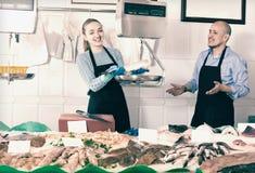 En ayudante y vendedor de ofrecimiento de los pescados de la tienda Foto de archivo libre de regalías