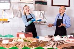 En ayudante y vendedor de ofrecimiento de los pescados de la tienda Fotografía de archivo libre de regalías