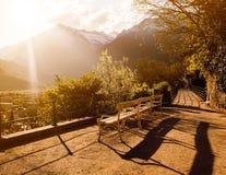 En bänk framme av kullarna under solnedgång Royaltyfria Bilder