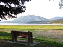 En bänk i härligt sceniskt område av sjön och berget Arkivbild