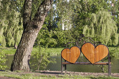 En bänk med två hjärtor på den för förälskade par Royaltyfria Bilder