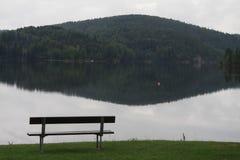 En bänk nästan en sjö Arkivbilder