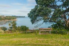 En bänk som förbiser havet, Whangaparaoa, Auckland, Nya Zeeland fotografering för bildbyråer