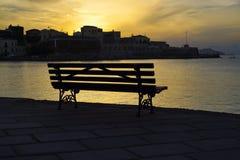 En bänk vid havet på solnedgången Arkivbild