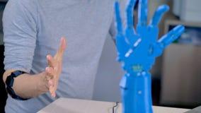 En bärande armbindelkontrollant för tekniker ger riktningar till en robotic hand lager videofilmer