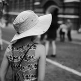 En bärande hatt för flicka som långt borta ser på gatan Arkivfoton