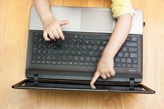 En bärbar dator och barns händer Arkivbilder