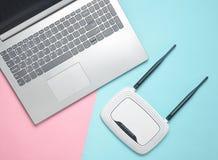 En bärbar dator och en router wi-fi på en kulör pappers- bakgrund Tangentbord touchpad digitala moderna teknologier kopiera avstå Arkivbild