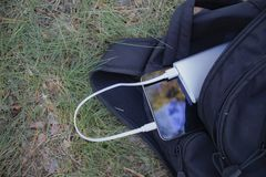 En bärbar uppladdare laddar minnestavlan Driva banken med kabel i påse, mot bakgrunden av naturen royaltyfri fotografi
