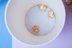 En bästa sikt av en kopp med kvarlevorna av popcornet på botten, purpurfärgad bakgrund, pappers- kopp, royaltyfria bilder