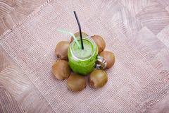 En bästa sikt av en naturlig grön drink från kiwi på en vit torkduk och på en träbakgrund Näringsrika exotiska frukter Arkivbild