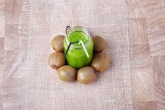 En bästa sikt av en naturlig grön drink från kiwi på en vit torkduk och på en träbakgrund Näringsrika exotiska frukter Royaltyfri Bild