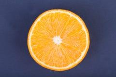 En bästa sikt av en organisk halva av apelsinen på en mörk purpurfärgad bakgrund Healthful och nya citrusfrukter arkivfoto