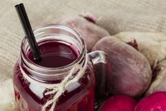 En bästa sikt av en murarekrus av nytt sammanpressade rödbetor dricker och några beta på ett tyg Ingredienser för strikt vegetari arkivbild