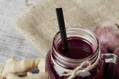 En bästa sikt av en murarekrus av nytt sammanpressade rödbetor dricker och några beta på ett tyg Ingredienser för strikt vegetari arkivfoton
