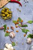 En bästa sikt av salladingredienser Gröna välfyllda oliv i en glass bunke bredvid mandelmuttrar och salladsidor på en grå färg Royaltyfri Fotografi