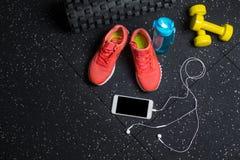 En bästa sikt av sportive tillbehör för idrottshallutbildning Sportskor, dum-klockor, flaska och telefon på en svart bakgrund Fotografering för Bildbyråer