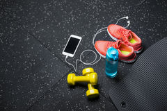 En bästa sikt av sportive tillbehör för idrottshallutbildning Sportskor, hantlar, flaska och en vit telefon på en svart Royaltyfri Foto