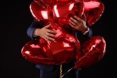 En bästa sikt på röda ballonger i manhänder på en svart bakgrund isolerat på vit som är selektiv fokusera Royaltyfri Bild