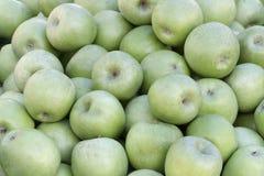 En backround av massor av gröna äpplen arkivfoton