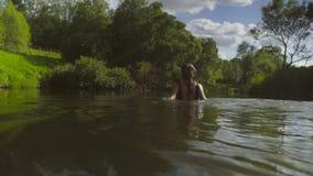 En badning för ung kvinna i en skogflod lager videofilmer