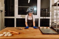 En bagare som gör kanelbruna rullar Arkivfoto