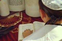 En bakre sikt av att be handen för ung man med en tefillin som rymmer en bibelbok, medan läsa en be på en judisk ritual Royaltyfri Bild