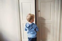 En bakre sikt av litet barnpojkeanseendet nära dörr inom i ett sovrum royaltyfri fotografi