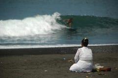 En Balinesedam och en surfare g?r morgonritual arkivbild
