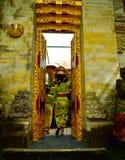 En Balinesekvinna som bär traditionella lokala kläder som skriver in en sakral tempel arkivfoton