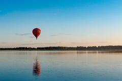 En ballong flyger över sjön arkivbilder