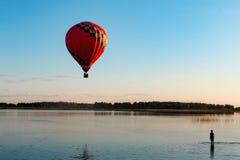 En ballong flyger över sjön arkivfoto