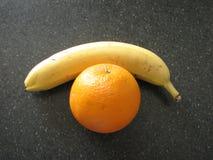En banan och en apelsin på tabellen royaltyfria bilder