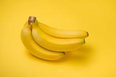 En banch av bananer på gul bakgrund Arkivfoton