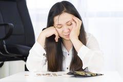 En bankrutt, bröt, och den frustrerade kvinnan har finansiella problem med mynt som lämnas på tabellen och en tom plånbok arkivfoto