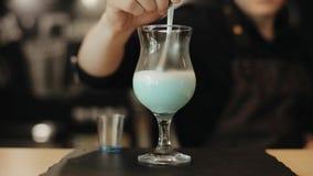 En baristaomrörning mjölkar i ett stångexponeringsglas med en sked En n?rbildsikt stock video