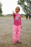 En barnflicka med den målade leopardframsidan som spelar i den kommunala lekplatsen, parkerar Arkivfoto